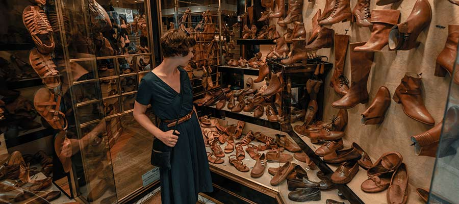A woman views a large selection of shoes.